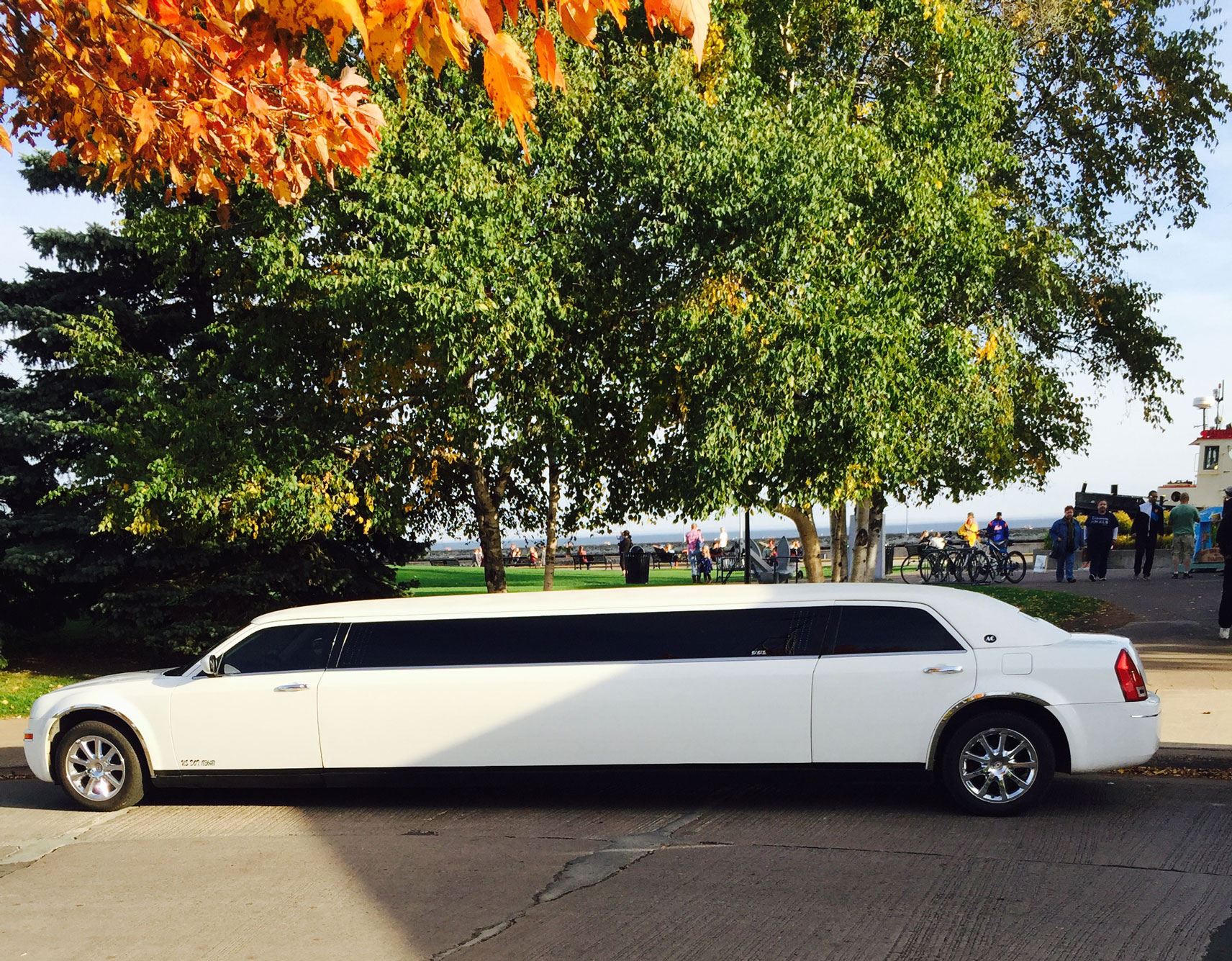 white Chrysler 300 Stretch limousine at festival by Lake Superior during the day