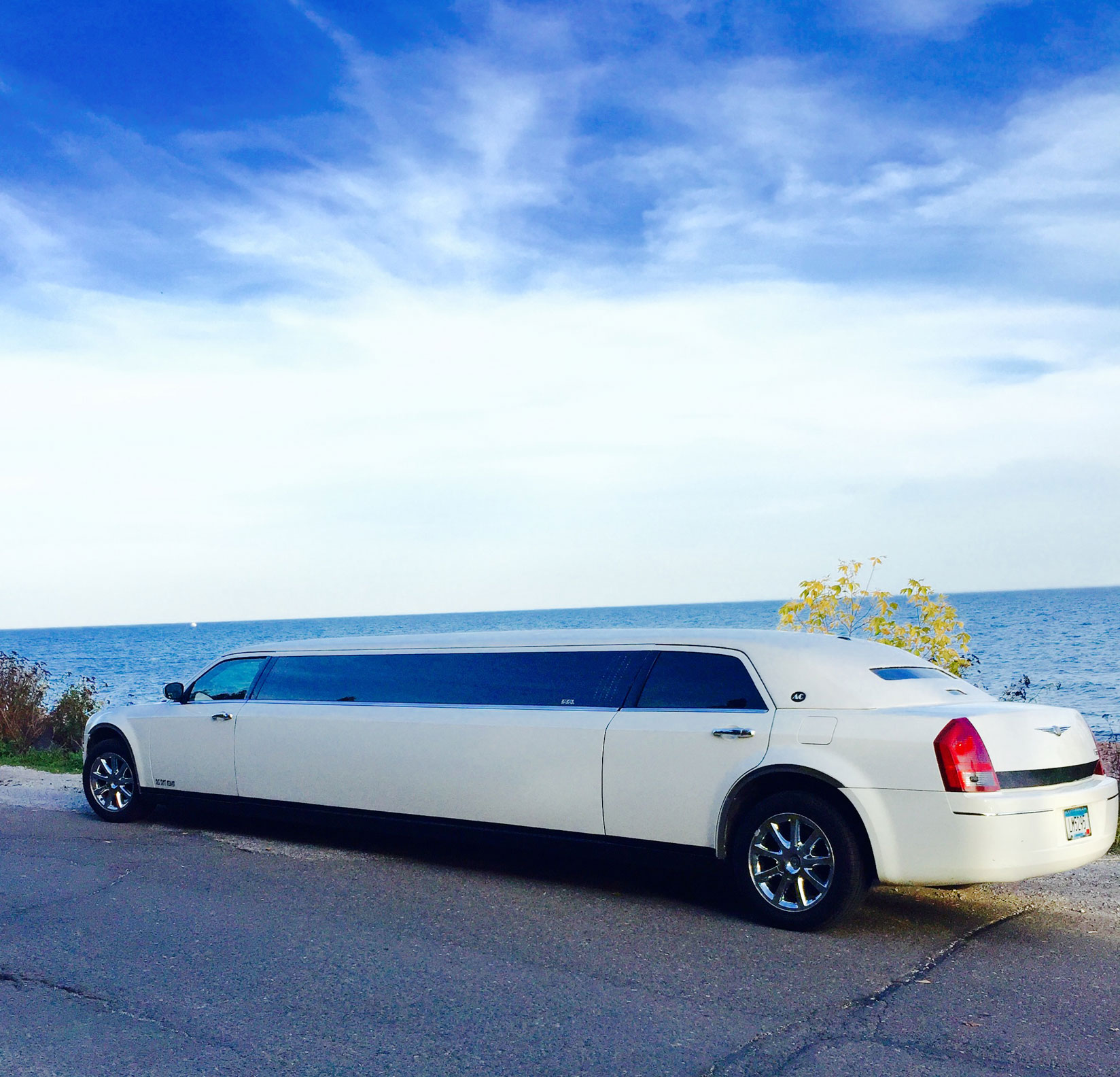 white Chrysler 300 Stretch limousine by Lake Superior during the day